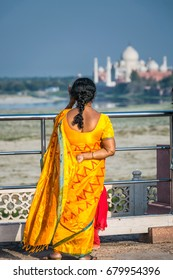 Local Indian woman shot from the back no face, wearing traditional sari looking at the distant Taj Mahal, an ivory-white marble mausoleum in the Indian city of Agra, Uttar Pradesh.
