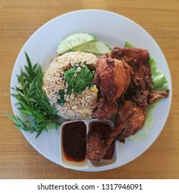 Local Indonesian and Malaysian delicacy called Nasi Goreng Ayam Penyet. Fried rice served with fried Chicken with vegetables.