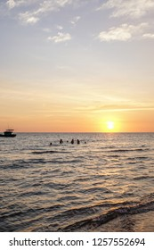 Local kids are playing in the water at sunset on Phu Quoc in Vietnam
