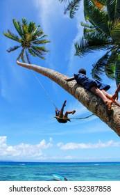 Local kids swinging on a rope swing in Lavena village, Taveuni Island, Fiji. Taveuni is the third largest island in Fiji.