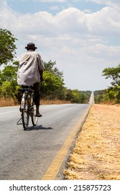 Local man riding on a bike on a desolated road in africa