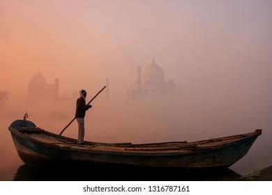 Local man standing in a boat on Yamuna River near Taj Mahal in early morning, Agra, Uttar Pradesh, India. Taj Mahal was designated as a UNESCO World Heritage Site in 1983.