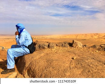 A local man is watching the Sahara Desert from the ruins of Djebel Baroun in Taghit.