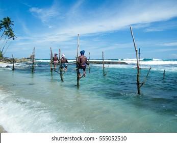 Local men fishing in traditional way. Fishermen at Hikkaduwa beach, Sri Lanka. Popular tourist destination.