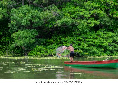 Local native Indian fisherman in a wooden boat throwing fish net into the river water. Lush green tropical forest in the background. Selective focus. Las Isletas, Granada, Nicaragua