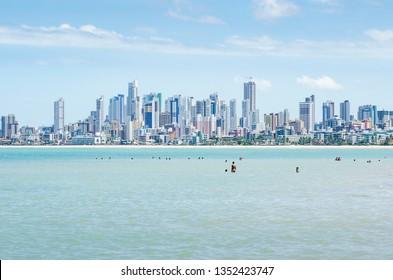 Local people and tourists at Praia do Bessa beach, Joao Pessoa PB, Brazil. Beachfront buildings on background.