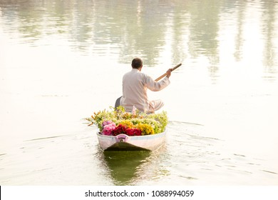 Local people use Shikara, a small boat for transportation in the Dal lake of Srinagar, Jammu and Kashmir state, India. A man carries a bouquet of flowers for sale in a boat.