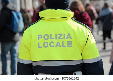 local police officer with a phosphorescent jacket that controls the streets of an Italian city