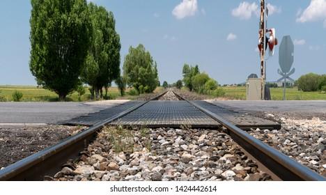 Local railway with the asphalt road crossing in a countryside, Afyonkarahisar, Turkey