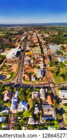 Local residential streets with houses and services and shops in Windsor regional town of Greater Sydney region on shores of Hawkesbury river in vertical aerial panorama to horizon.