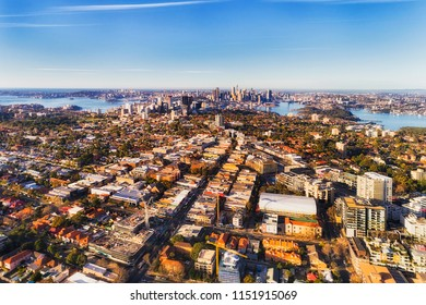 Local residential suburbs in Inner city of Sydney on shores of Sydney harbour viewed from above mid-air on a sunny day facing CBD landmarks.