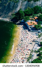 Local residents and tourists relax at Praia Vermelha beach against a backdrop of Sugarloaf Mountain, one of the most popular tourist attractions in the city.