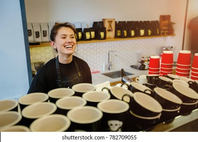 Local, small business concept - portrait of cheerful laughing female barista waiting for client while having job in cafe. Labor concept. View from above. A lot of empty cups in the foreground.