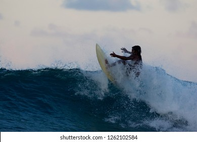 Local surfer at sunset rides a wave at Inside Mikados break, Thaa Atoll, Maldives, Indian Ocean, Asia