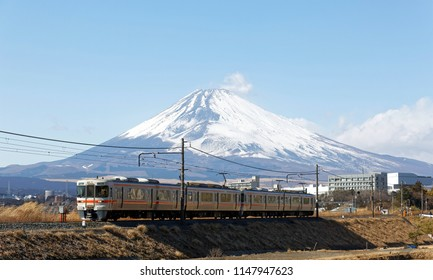 A local train (313 Series) of JR Gotemba Line travels through the countryside on a sunny winter day with majestic snow capped Mount Fuji in background under blue clear sky in Sasono, Shizuoka, Japan