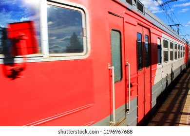 Local Train Arriving at Platform on Railway Station. Summer Day View of Old Red Train with Doors Closed and Sky Reflecting on the Windows. Train Waiting on Railroad Track