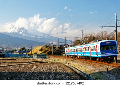 A local train of Izu-Hakone Railway traveling through harvested farmlands with the snow capped mountaintop of Fujisan veiled by clouds in background on a sunny winter day, in Mishima, Shizuoka, Japan