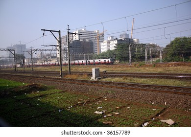 The local train running on one of the many railroads in Mumbai (Bombay), India.