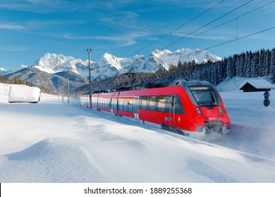 A local train traveling by a forest in a valley covered by deep snow on a sunny winter day and Karwendel Mountain dominating the background under blue sky near Garmisch-Partenkirchen, Bavaria, Germany