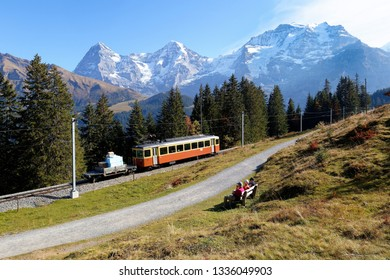 A local train travels on the narrow gauge railway by the green grassy hillside, with majestic Eiger, Monch & Jungfrau mountains under blue sky in background, near Murren, Bernese Highland, Switzerland