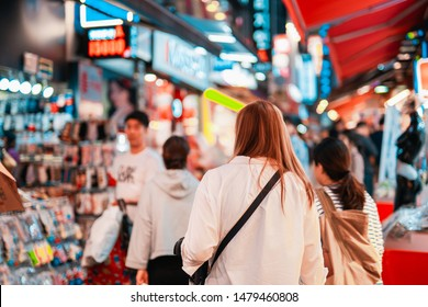 local travel activity concept from asian woman shopping and eat street food at night of south korea market