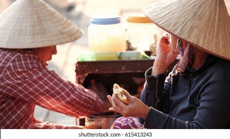 Local Vietnamese women eating baguette bread with vegetable and meat filling (called Banh My or Banh Mi in Vietnamese) - popular street food in Vietnam.