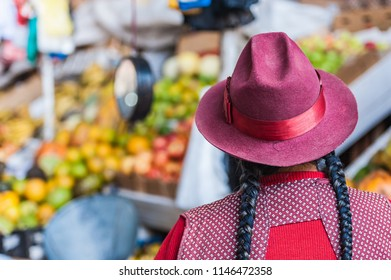 Local woman selling fruits, vegetables and local delicacies. Displayed on a counter at a vintage South American market. Cusco, Peru