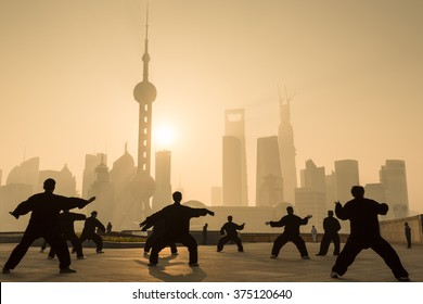 Locals exercise performing martial arts on Shanghai's riverfront as the sun rises.