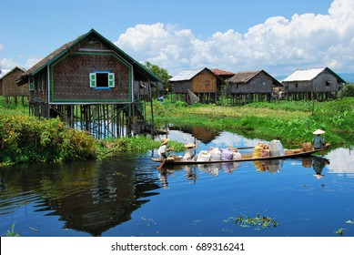 Locals transporting goods on a small boat through a floating village on the Inle lake, Myanmar.