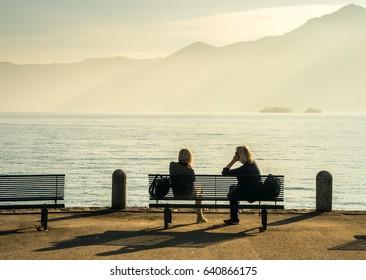 LOCARNO - APRIL 7 : Lake Maggiore side scene with unrecognized people relax on bench in Locarno, Switzerland, on April 7, 2017.