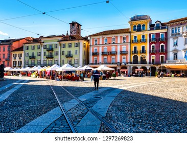Locarno, Switzerland - 03/08/2018: Piazza Grande is the main square of Locarno. In the picture we see the old houses and people walking around the square. The weekly market  takes place every thursday