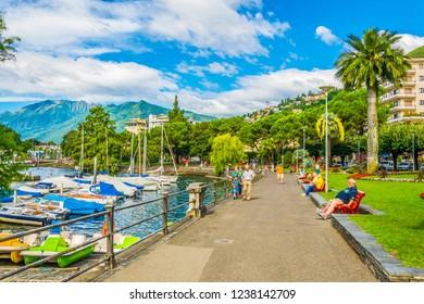 LOCARNO, SWITZERLAND, JULY 26, 2017: People are strolling through promenade alongside Locarno lake in Switzerland