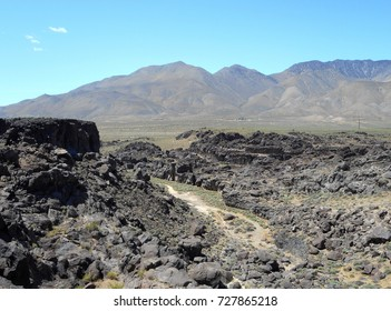 Located near the Sierras in California hiking trail featuring lava rock and a dry river bed.