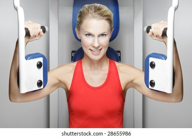 Location shoot of caucasian blonde model doing chest press and looking at the camera