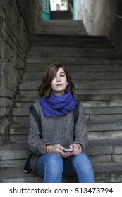 Location shot of a lonely sad teen girl wearing grey sweater and blue scarf sitting on steps with her backpack