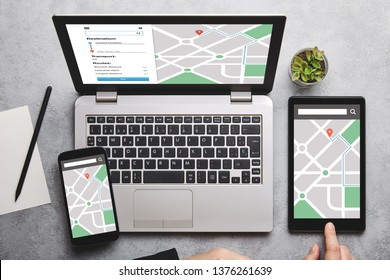 Location tracker concept on laptop, tablet and smartphone screen over gray table. All screen content is designed by me. Flat lay