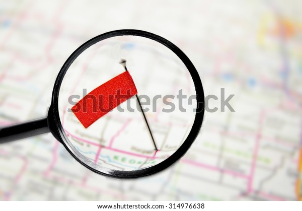 locator pin flag in a map with magnifying glass