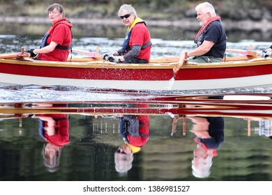 LOCH AWE, ARGYLL, SCOTLAND, UK : 28 APRIL 2019 : The crew and skiff from the Queensferry Boat Club cast their reflections in the water as they take part in the Loch Awe Adventure and Dalavich Regatta