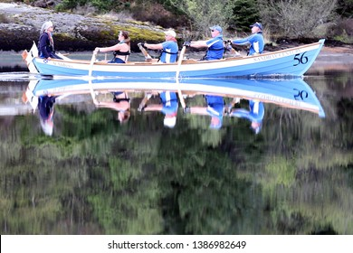LOCH AWE, ARGYLL, SCOTLAND, UK : 28 APRIL 2019 : The crew and skiff from the St Andrews Boat Club cast their reflections in the water as they take part in the Loch Awe Adventure and Dalavich Regatta