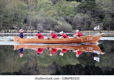 LOCH AWE, ARGYLL, SCOTLAND, UK : 28 APRIL 2019 : The crew and skiff from the Arran Boat Club cast their reflections in the water as they take part in the Loch Awe Adventure and Dalavich Regatta