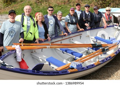 LOCH AWE, ARGYLL, SCOTLAND, UK : 28 APRIL 2019 : The Dalavich crew stand by their skiff on the shore prior to the Loch Awe Adventure