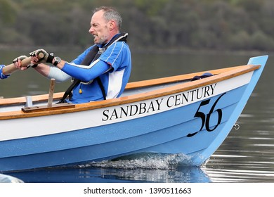 LOCH AWE, ARGYLL, SCOTLAND, UK : 28 APRIL 2019 : The front oarsman on board the St Andrews skiff Sandbay Century puts in some effort during the Dalavich Regatta on Loch Awe