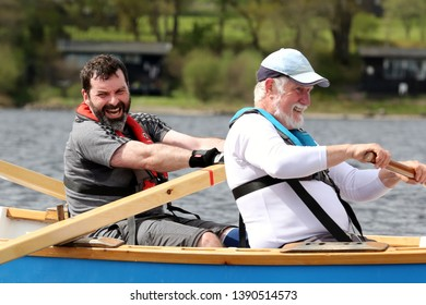 LOCH AWE, ARGYLL, SCOTLAND, UK : 28 APRIL 2019 : Two rowers belonging to a skiff crew put the hard work and effort in during the Dalavich Regatta on a Loch Awe