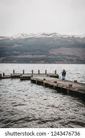 Loch Lomond, Scotland - March 17, 2018: Man walking on a pier on Loch Lomond in Scotland. The Loch forms part of the Loch Lomond and The Trossachs National Park