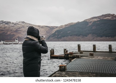 Loch Lomond, Scotland - March 17, 2018: Man taking photos on a pier on Loch Lomond in Scotland. The Loch forms part of the Loch Lomond and The Trossachs National Park.