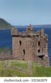 Loch Ness, Scotland - June 2, 2012: The ruins of the main tower and house of Urquhart Castle sit on a cliff looking over deep blue Loch Ness. Surrounding green hills. Light blue sky.