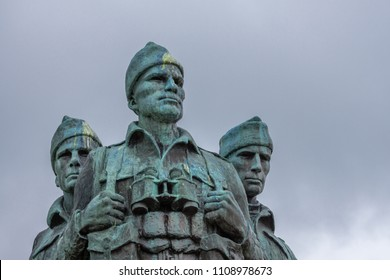 Lochander, Scotland - June 11, 2012: Closeup of three soldier heads at green-gray bronze Commando Memorial statue along A82 and near Spean River under cloudy sky.