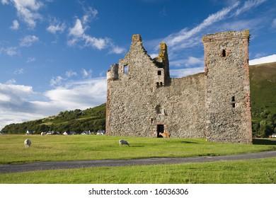 Lochranza Castle with animals in evening sunlight