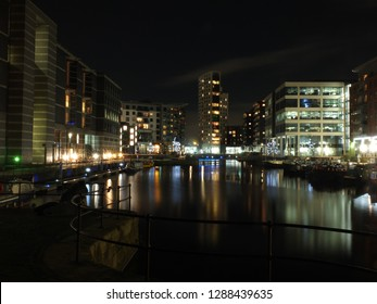 the lock entrance and moorings at clarence dock in leeds at night with buildings of the development reflected in the water and glowing street lights and boats