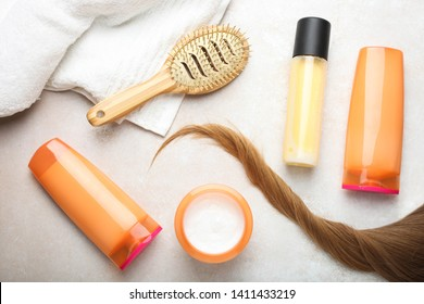 Lock of female light brown hair, set of hair care products, bamboo comb and terry towel on  neutral background. Top view.